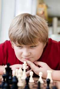 Middle school boy contemplating his next chess move.