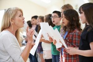 Children in singing group being encouraged by teacher.
