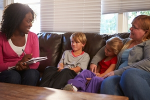Photo of African American social worker with two children and their mother on a couch.